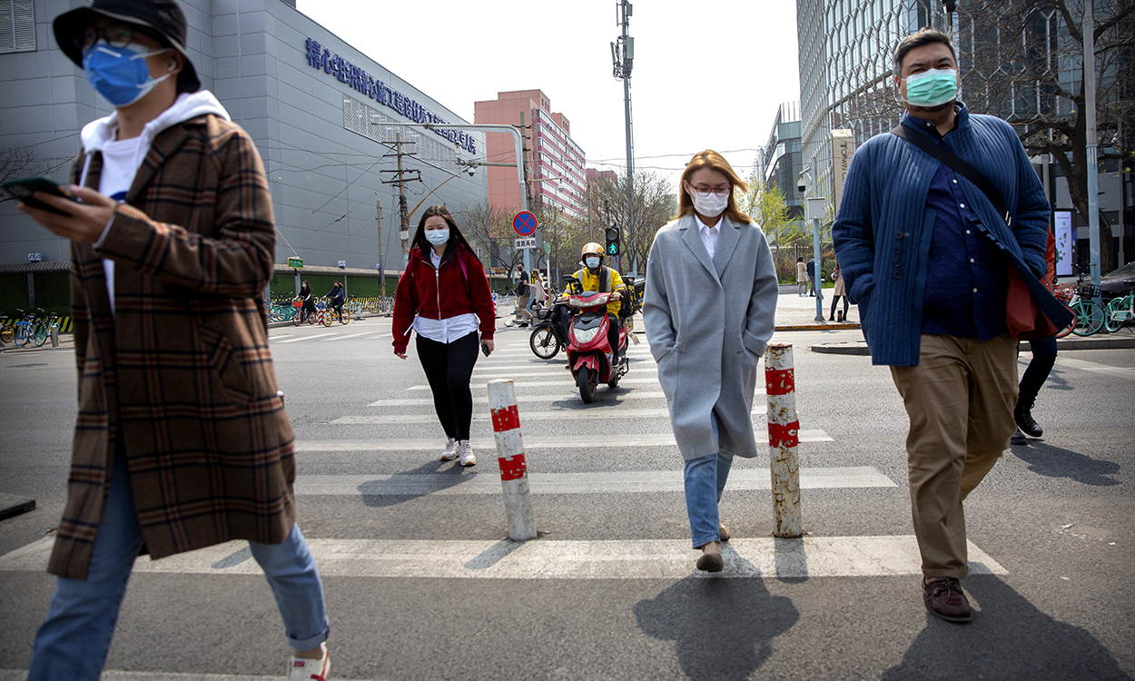 People wear face masks as they walk across an intersection in Beijing, Tuesday, April 7, 2020. China on Tuesday reported no new deaths from the coronavirus over the past 24 hours and  just a few dozen new cases, all from people who returned from overseas. (AP Photo/Mark Schiefelbein)