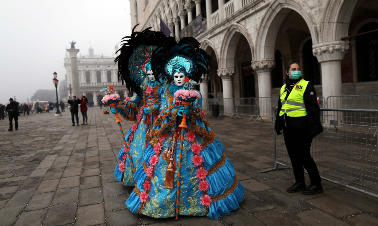 A policewoman wearing a protective mask stands next to carnival revellers at Venice Carnival, which the last two days of, as well as Sunday night's festivities, have been cancelled because of an outbreak of coronavirus, in Venice, Italy February 23, 2020. REUTERS/Ohad Zwigenberg ISRAEL OUT. NO COMMERCIAL OR EDITORIAL SALES IN ISRAEL