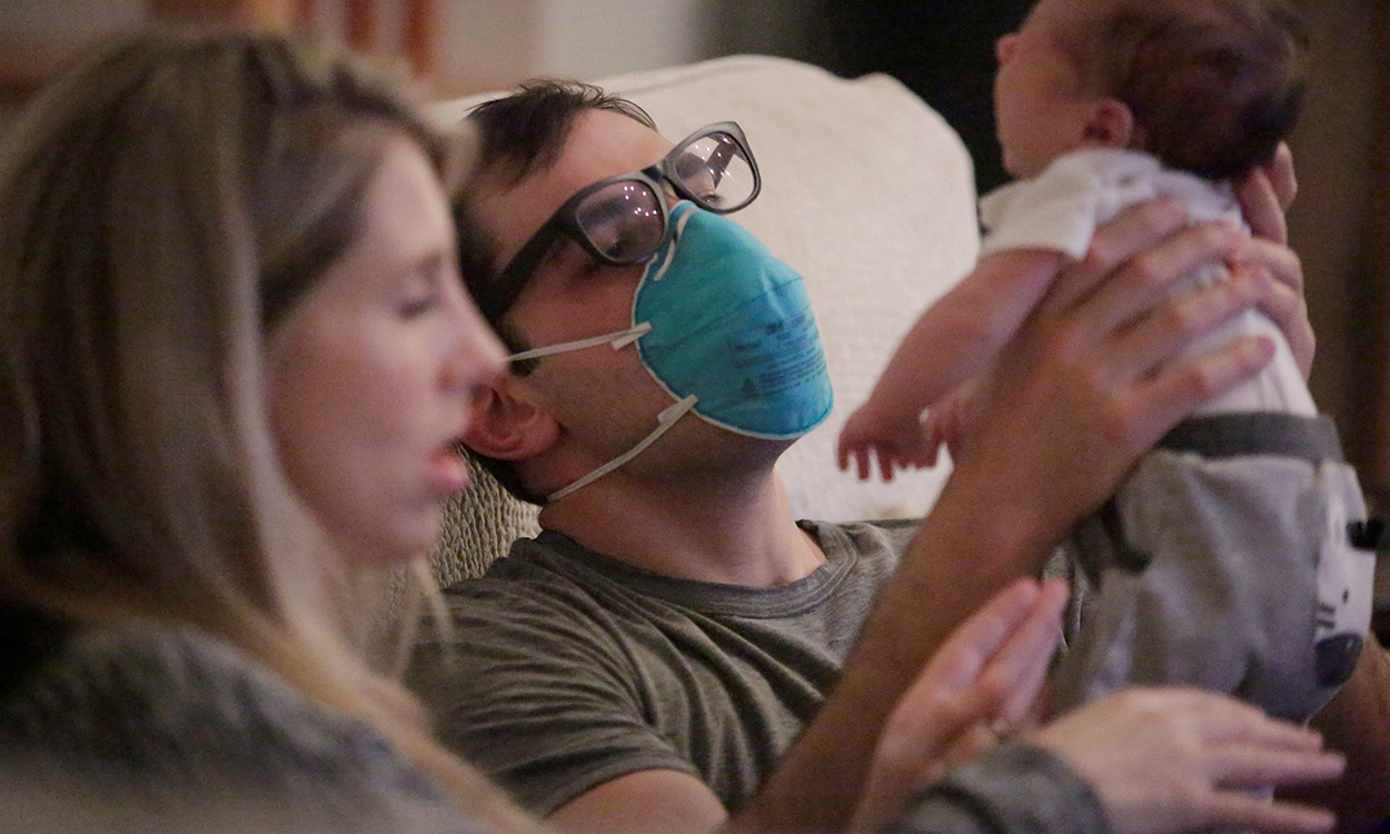 Emergency medicine physician Thomas Krajewski wears a mask as he holds his baby Cal with his wife Genevieve after finishing his shift amid an outbreak of coronavirus disease (COVID-19) in New Orleans, Louisiana, U.S., March 27, 2020. Picture taken March 27, 2020.  REUTERS/Kathleen Flynn     TPX IMAGES OF THE DAY