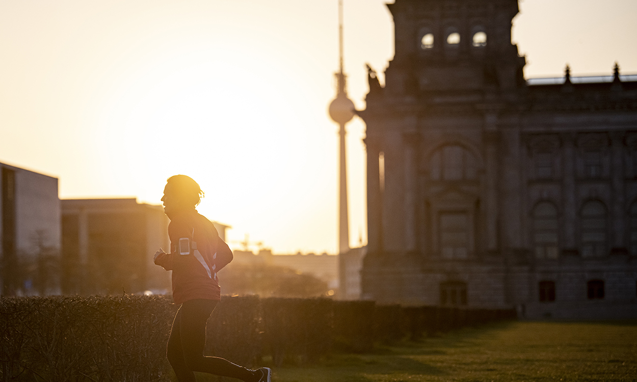 08 April 2020, Berlin: A jogger runs past the Bundestag in the morning. Photo: Fabian Sommer/dpa