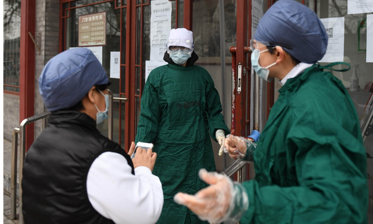 Medical staff wear facemasks to protect against the COVID-19 coronavirus as they chat outside a hospital in Beijing on February 20, 2020. - China on February 20 touted a big drop in new virus infections as proof its epidemic control efforts are working, but the toll grew abroad with deaths in Japan and South Korea. (Photo by Greg Baker / AFP)