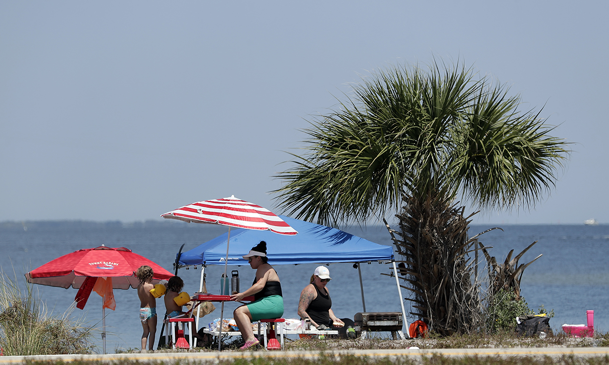 Despite a stay at home policy due to the corona virus in Florida, residents picnic along the Beachline Expressway on the Indian River Saturday, April 4, 2020, near Cape Canaveral, Fla. (AP Photo/John Raoux)
