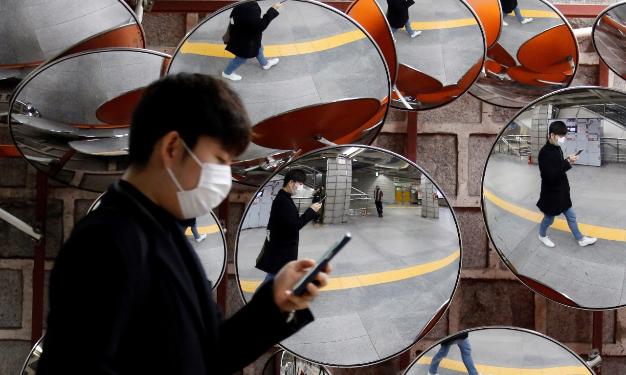 A man wearing a mask to prevent the coronavirus is reflected in the mirrors, in Seoul, South Korea, February 24, 2020.    REUTERS/Heo Ran